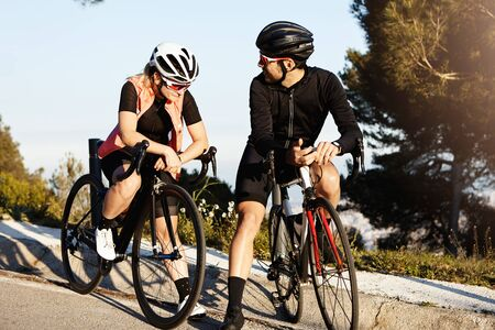 Couple on racing bicycles having rest on their morning cycle ride in park, both dressed in cycling equipment, wearing special sunglasses, man looking back at his female friend and telling something Imagens
