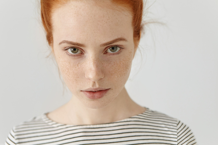 Human face expressions and emotions. Portrait of young redhead woman in sailor shirt having confident serious face, posing isolated at white studio wall, looking at camera from under her eyebrows