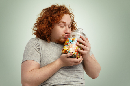 Funny plump young Caucasian male with curly ginger hair kissing glass jar of sweets and marmalades, clasping it gently to heart. Obesity, gluttony, food, nutrition and unhealthy lifestyle concept Stockfoto