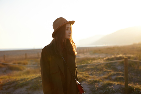 Peaceful young female wearing sylish hat, coat and shoulder bag having joyful carefree look while relaxing outdoors on coastline on spring sunny day, waiting for friends. People and lifestyle concept