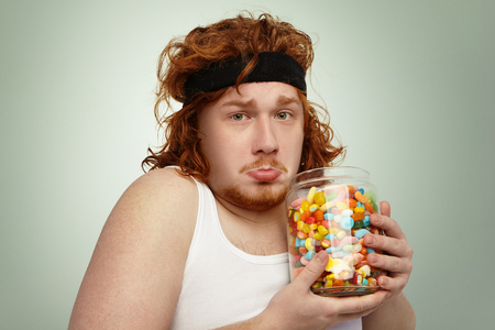 Portrait of unhappy overweight obese young red-haired European man wearing hairband and white tank top after physical exercises, feeling frustrated while cant stop consuming delicious sweets