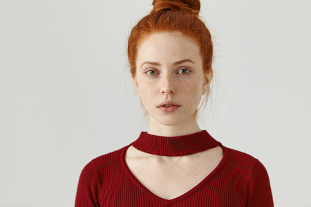 Headshot of fashionable gorgeous young ginger Caucasian female with hair bun and freckles dressed in maroon dress with trednd cut out. People, youth, beauty, style, fashion and clothing design concept
