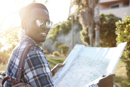 Attractive stylish Afro American tourist looking at camera with happy joyful smile while having nice walk in urban surroundings of foreign city, searching for locations using paper map. Flare sun