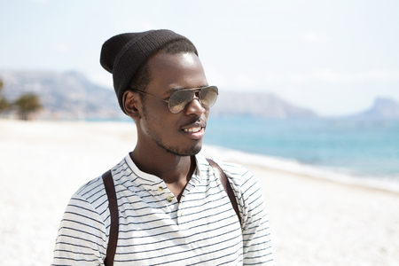 Handsome black hipster wearing stylish hat, sailor shirt, shades and backpack walking alone on urban beach, admiring Maritime seaside landscape while traveling abroad during summer vacations Stockfoto