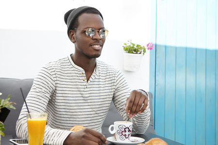 Fashionable black man in round sunglasses, striped shirt and headwear having rest at sidewalk cafe, enjoying coffee, having cheerful look, feeling relaxed and carefree during trip in foreign country Stockfoto