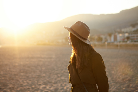 Caucasian woman traveling alone, visiting European town, walking down sea shore in fall or spring. Half-profile portrait of businesswoman on business trip having rest during evening walk at seaside