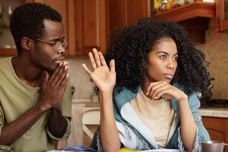 People, relationships problems and divorce. Repentant worried dark-skinned male keeping hands pressed together, begging offended wife to forgive his infidelity, mad woman not looking at him at all