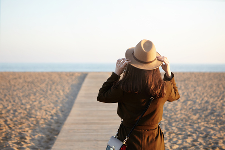 Outdoor image of unrecognizable Caucasian female novel writer visiting European sea beach for inspiration, wearing stylish classic outwear and bag, walking down boardwalk. People and lifestyle