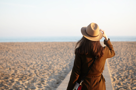 Side view of beautiful female stranger on autumn sand beach. Brunette woman looking into distance, noticed ship or dolphin in sea or ocean, adjusting her beige hat with hand, mind full of thoughts Stockfoto