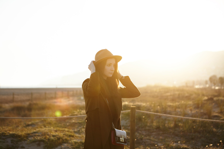 Confident attractive young brunette woman student with pretty face adjusting her hat during morning walk on urban beach before university. Stylish girl enjoying warm sunny day outdoors. Flare sun Stockfoto