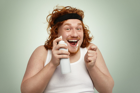Cheerful chubby young European man with curly ginger hair having fun indoors, holding spray can, his face dirty with white whipped cream, looking at camera with happy and excited facial expression
