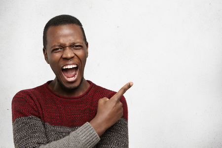 Negative human emotions. Headshot of desperate furious young dark-skinned male dressed casually pointing his index finger sideways at white copy space wall, feeling mad and angry with something Stockfoto