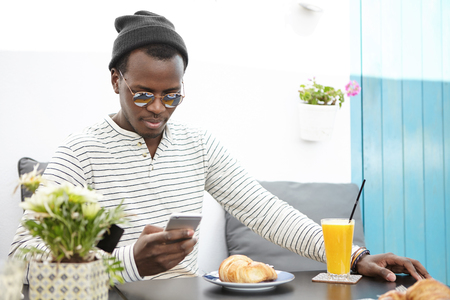 People, lifestyle, travel, vacations and modrn technology concept. Handsome dark-skinned tourist wearing stylish hat and sunglasses texting sms on mobile phone during breakfast at sidewalk cafe