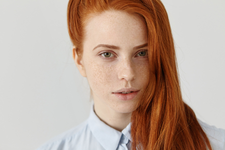 Beautiful ginger girl with freckles all over her pretty face standing at white studio wall dressed in formal light-blue shirt, wearing red hair loose on side, looking at camera with mysterious smile