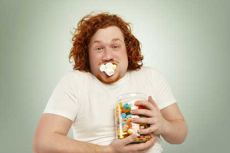 Never enough. Close up shot of funny young plump man with curly ginger hair holding tight jar of candies, looking at camera with startled surprised expression, his mouth stuffed with marshmallow