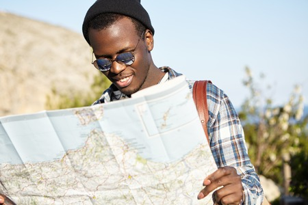 Attractive smiling young Afro-American hipster in stylish black hat and sunglasses consulting big paper map while sightseeing in foreign country, looking for right direction, enjoying summer vacations