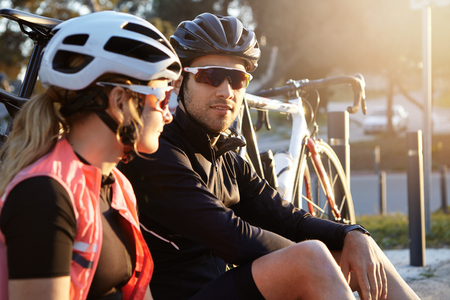 Side view headshot of sportive and healthy European couple sitting on grass near their bicycles in helmets and sunglasses, talking about their plans. People, sports, fitness and active lifestyle Stockfoto