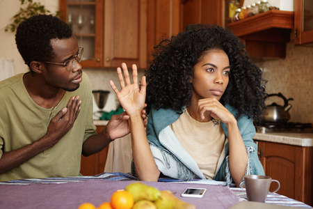 Regretful unhappy young African American male in glasses trying hard to sweet talk his mad offended wife who is sitting next to him at kitchen table, refusing all his lies. People and relationships
