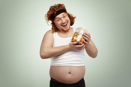 Happy handsome red-haired man wearing hairband and shrunk tank top holding glass jar of candies, rejoicing at delicious but unhealthy junk foot after cardio training, fighting excess weight