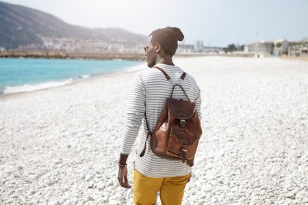 Rear view of fashionable black male student wearing brown leather backpack and stylish hat on warm spring day having nice walk on urban beach after lectures at University, admiring beauiful sea view Stockfoto