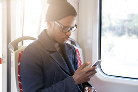Serious young black male in trendy rectangular glasses looking through pcitures via social media, using cell phone while riding home by bus. People, travel, transportation and public transport