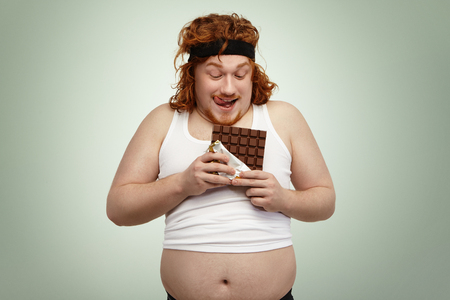 Happy redhead young man in sports wear holding bar of chocolate, about to have some, anticipating its sweet taste after intensive cardio workout in gym. Obese overweight male enjoying junk food Imagens