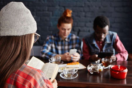 Multiethnic group of stylish young students drinking tea at cafe during break: girl in hat reading book while redhead woman and African man using electronic gadgets. People and modern technologies Imagens