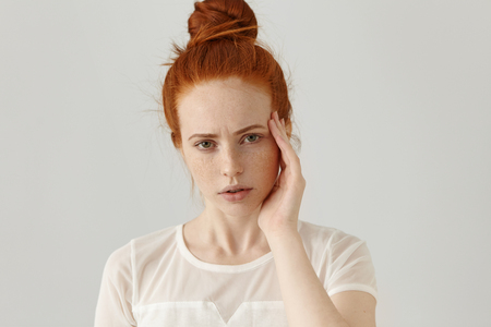 Headshot of unhappy young red-haired female having frustrated and painful expression, frowning, touching temple with hand, suffering from bad headache or migraine while facing stress at work