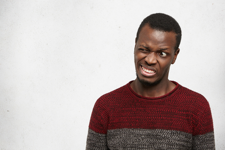 Studio portrait of crazy funny young African American man wearing casual sweater posing indoors grimacing, making mouths, clenching teeth and winking. Human facial expressions, emotions and feelings