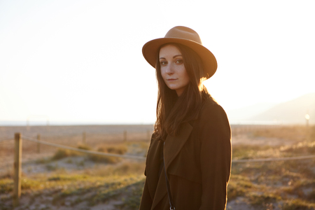 Outdoor portrait of beautifulCaucasian girl wearing fashionable coat and hat feeling carefree and peaceful, contemplating amazing morning view at seaside, looking at camera with charming smile