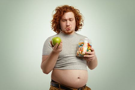 Studio shot of thoughtful indecisive redhead overweight fat man with big stomach feeling confused and hesitant, facing difficult choice: whether to eat healthy organic apple or unhealthy sweets