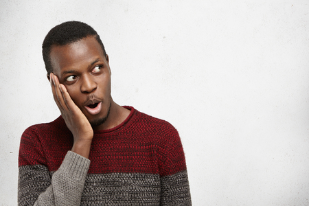 Stunned bug-eyed young Afro-American man looking sideways in full disbelief, having astonished shocked expression, keeping mouth opened and jaw dropped. Human emotions, feelings, reaction and attitude Stockfoto