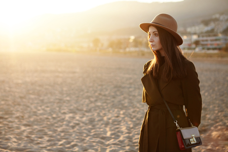 Woman on empty sea beach. Young lady with aristocratic traits in stylish outwear and hat standing on sandy beach in tranquility, having calm and peaceful face expression, admiring beautiful sunset