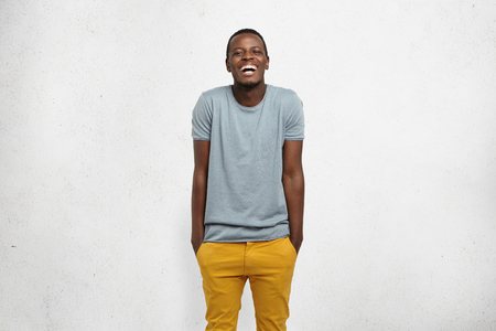 Human feelings and emotions. Body language. Studio shot of young cheerful African male, dressed casually, hands in pockets of yellow pants, shrugging, laughing at camera, isolated on white background