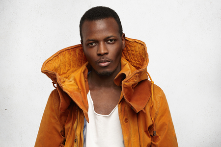 Headshot of attractive confident young Afro-American student wearing trendy winter orange hooded coat before going out to college. Black man model posing in studio. Season, clothing, style and fashion