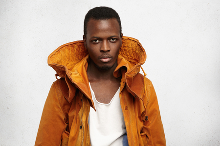Studio shot of handsome young dark-skinned man wearing fashionable orange jacket with hood, looking at camera with serious and confident face expression. Black male trying on overclothes indoors