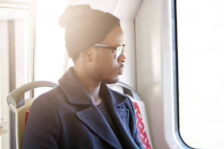 People, lifestyle and travel concept. Sideview of handsome dark-skinned man in stylish clothing sitting by window in bus or train while traveling in foreign country, admiring beautiful view outside
