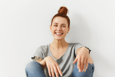 Fashionable beautiful young red-haired Caucasian woman with hair bun enjoying free time at home, sitting on floor and leaning back on white wall, looking at camera with happy cheerful smile