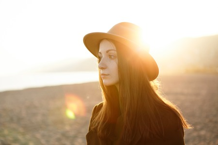 Half-profile portrait of sad and disappointed young tender Caucasian woman with deep-in-thoughts face expression, sun rays touching her head in brown stylish hat, isolated on background of riverside
