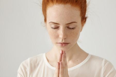 Close up Schuss von religiöser junger Ingwer Frau in der weißen Bluse meditierend oder beten halten die Augen geschlossen und die Hände zusammengepresst, das Beste zu hoffen. Menschen, Religion, Spiritualität, Gebet Standard-Bild - 76078513