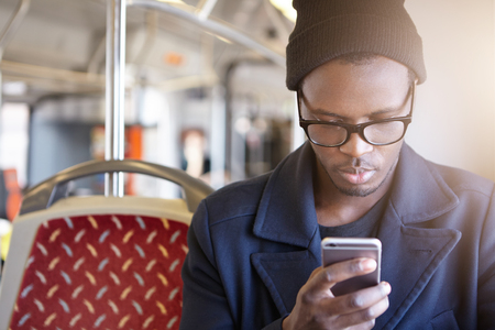 Attractive young African American tourist wearing black hat, stylish glasses and coat using smart phone in bus to book airplane tickets or do online check in. People, lifestyle and modern technology