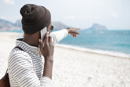 Unrecognizable dark-skinned young male tourist dressed in trendy clothing standing on white sandy beach and pointing his index finger into distance towards ocean while having phone conversation