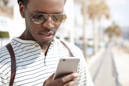 Attractive young Afro American traveler in trendy shades using navigation app on his generic mobile phone, looking for direction while walking in foreign city alone. People and modern technology