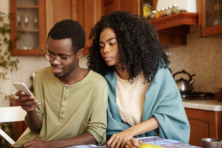 Suspicious black wife with Afro hairstyle trying to read message that her happy husband sending to someone on mobile phone as she suspects betrayal, not trusting him. Jealousy, infidelity and distrust Stockfoto