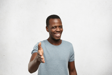 Friendly attractive African American man giving hand for handshake as sign of greeting, smiling widely and sincerely, looking very glad to see person he meeting. Human emotions and face expressions