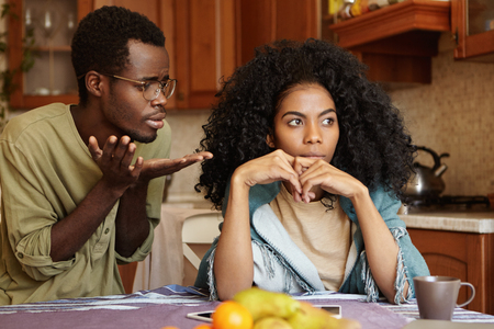 Candid shot of unhappy young Afro-American couple having quarrel at home: guilty regretful man wearing glasses begging his angry wife for forgiveness, apologizing to her for making bad mistake Imagens