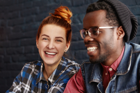 Stylish young interracial couple having fun at coffee shop: beautiful Caucasian female with hair bun smiling cheerfully while on date with handsome Afro-American man. Selective focus on girls face