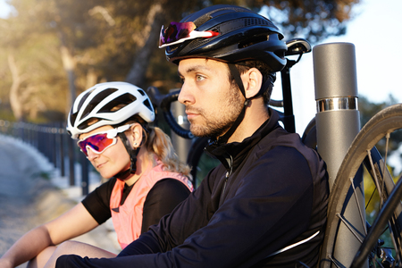 Healthy and active lifestyle. Two cycle-travelers resting on bridge in morning after long ride, selective focus on handsome and charismatic young bearded man with positive thoughtful face expression Stockfoto