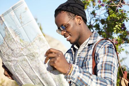 Cheerful happy young African American traveler having trendy look searching for direction on location map, looking how to get to hotel while traveling abroad in a foreign city duringsummer vacation Stockfoto