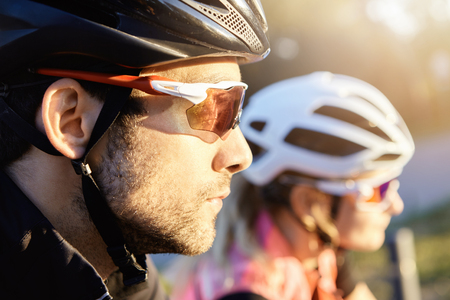 Headshot of young attractive bearded Caucasian man cyclist taking part in bicycle parade, selective focus on his head in helmet. Human and active leisure. Summer sports. Healthy lifestyle concept Stockfoto